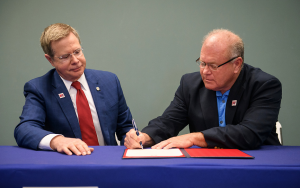 Chancellor and man signing papers